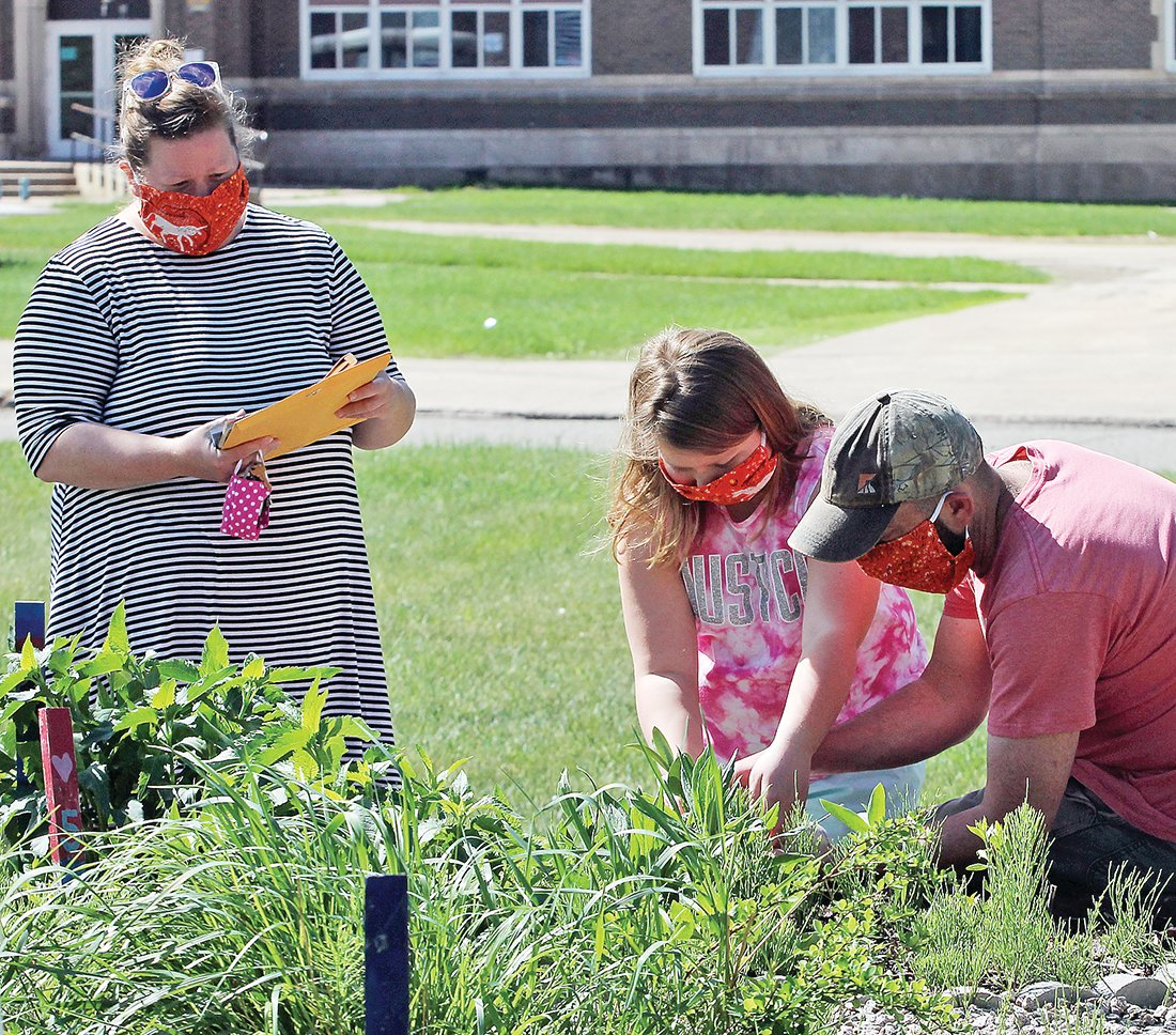 Tara and Kevin Boerst help their daughter Anika plant some flowers.