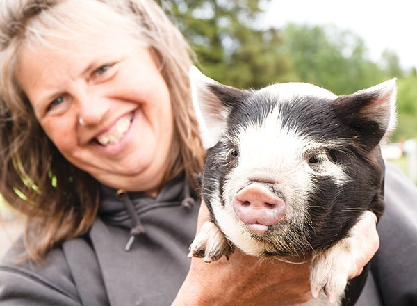 Lois Pajari with a two-week-old New Zealand Kune Kune pig.