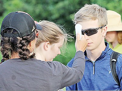 Ely assistant cross country coach Megan Devine checks the temperature of a cross country runner ahead of a 