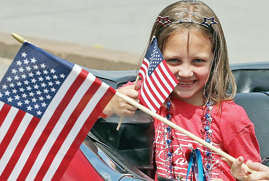 A smiling flag waver in the mini-parade for the Carefree Living facility in Ely.