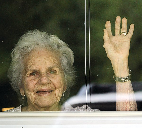 Ely Carefree Living resident Barbara Kollar waves from the window of her room.