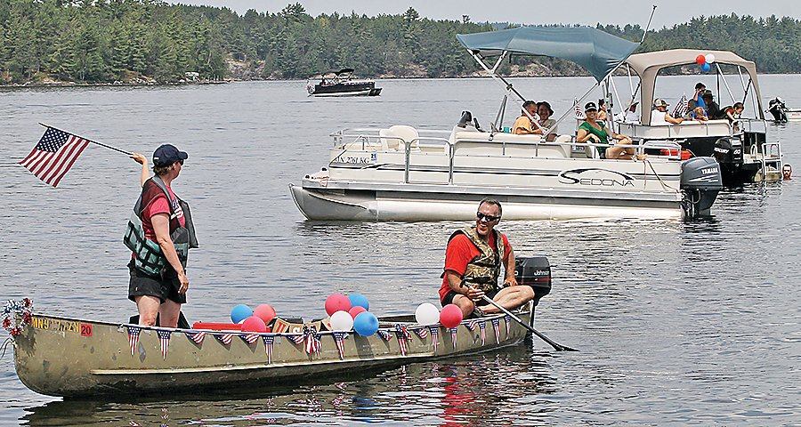 Andy and Sarah Levar show the colors during a July 4 flotilla on Burntside Lake.