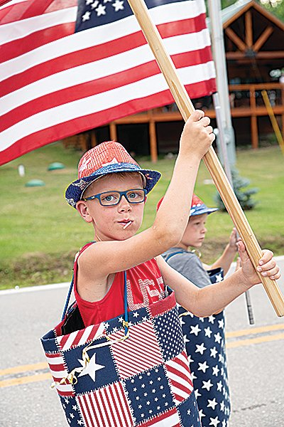 A young flag bearer marched in the Crane Lake parade.