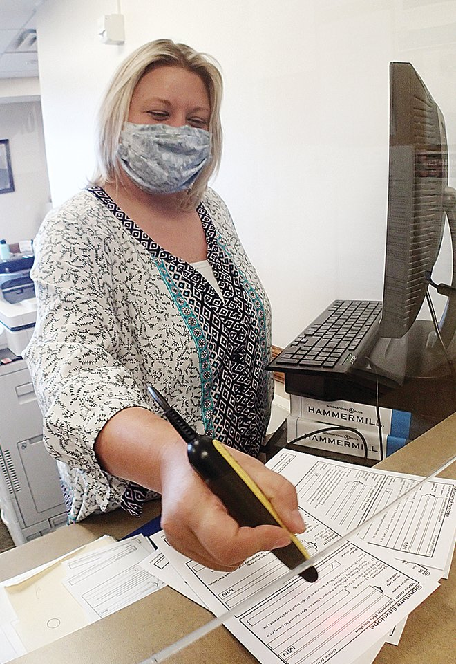Ely Deputy Clerk Casey Velcheff scans ballot bar codes Monday as she registers a stack 