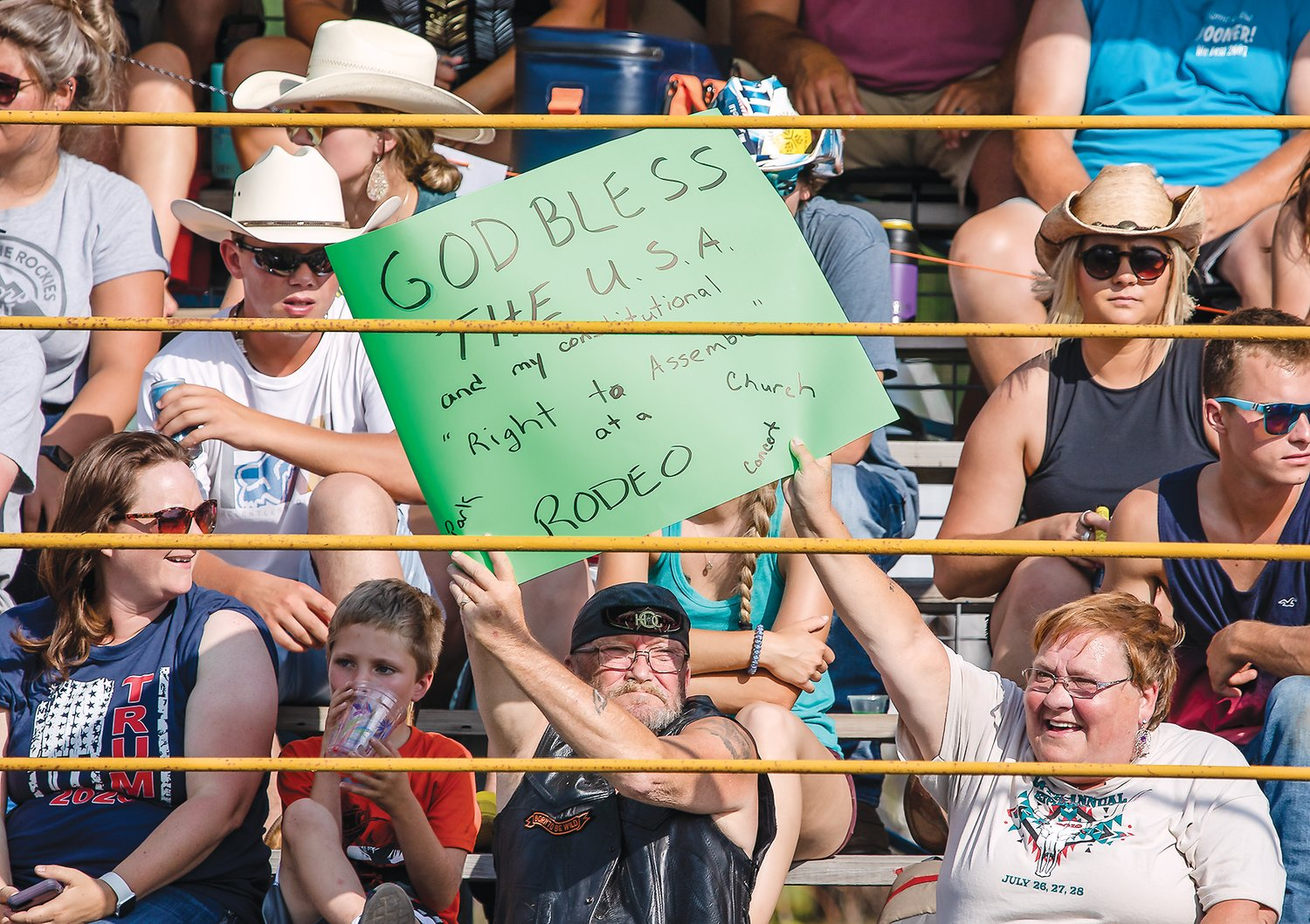 "Audience members at the North Star Stampede hold up a sign that reads ""God bless the USA and my constitutional right to assemble at a rodeo, park, church, concert."""