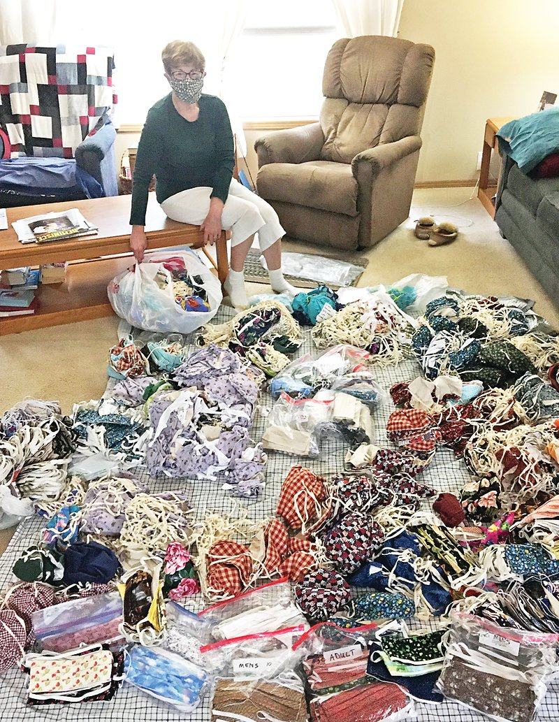 Gail Haney poses with hundreds of masks she made and donated.