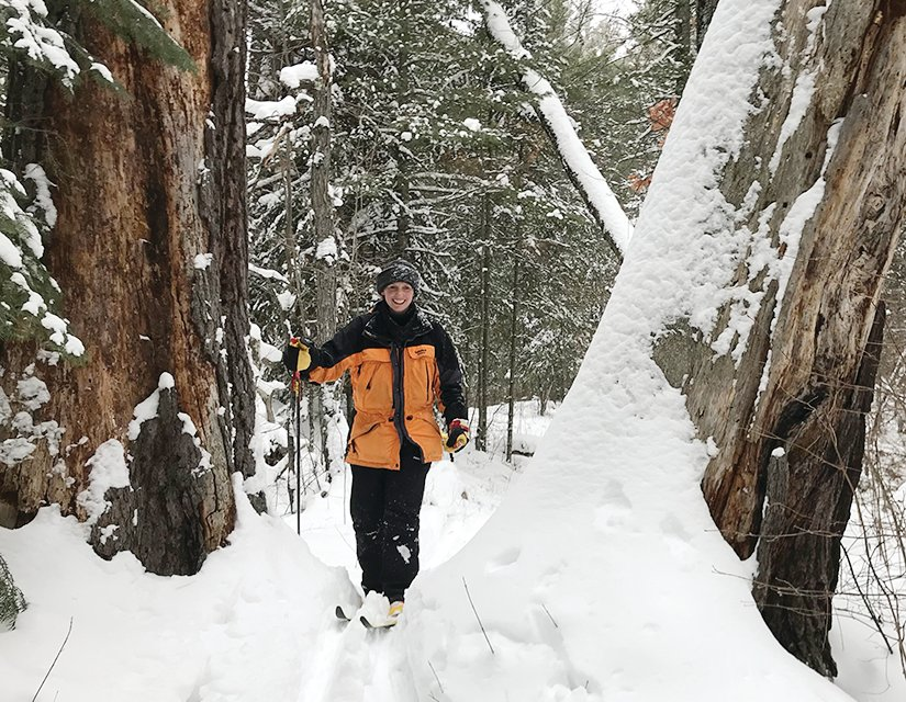 Skiing through a pair of huge pine snags along the Ole Lake Loop, one of the most 