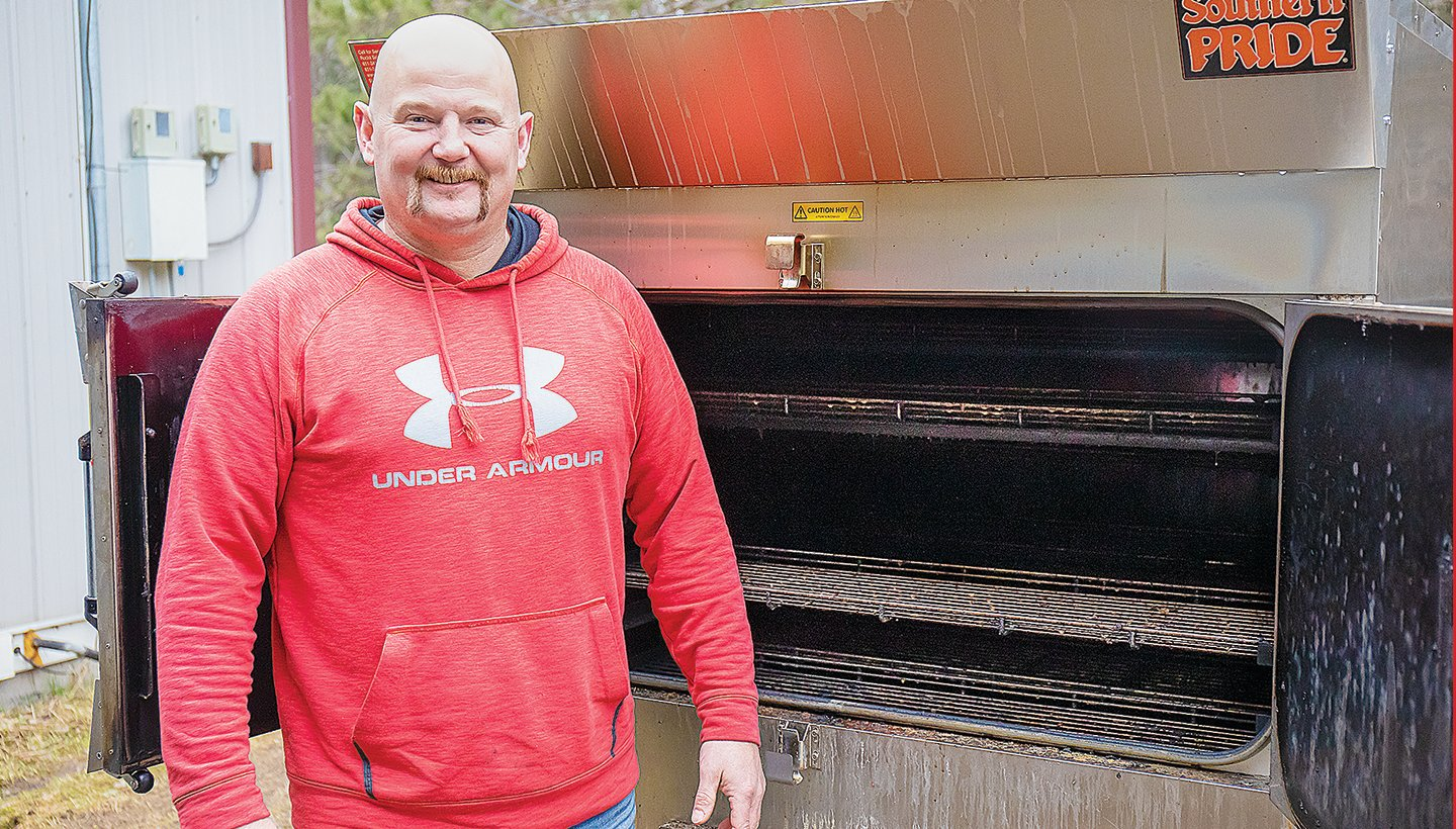 Restaurant co-owner Eric Drake stands in front of a commercial-grade smoker that can handle up to 500 pounds of meat at a time.