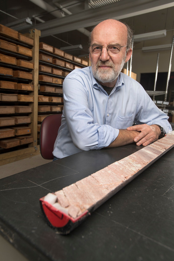 Rutgers University–New Brunswick professor Dennis Kent with part of a 1,700-foot-long rock core through the Chinle Formation in Petrified Forest National Park in Arizona. The background includes boxed archives of cores from the Newark basin that were compared with the Arizona core.