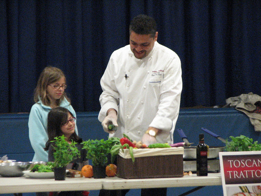 Students Emily Fusco and Isabel Voca assist Chef Jose Velez at Lincoln School