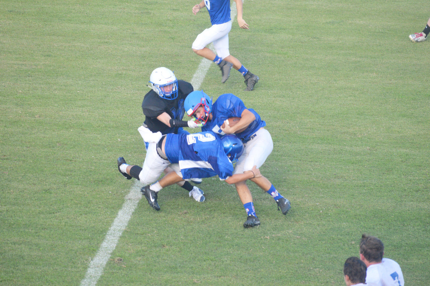 Josh Medlin (5) is brought down by a pair of Hawkins Hawks in Thursday's scrimmage.