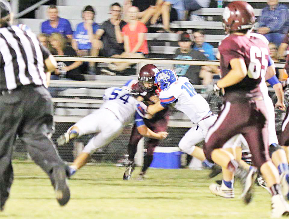 David Tarno (54) and Dylan Coe (18) stop a Cumby runner cold in the Bulldogs win Friday night.