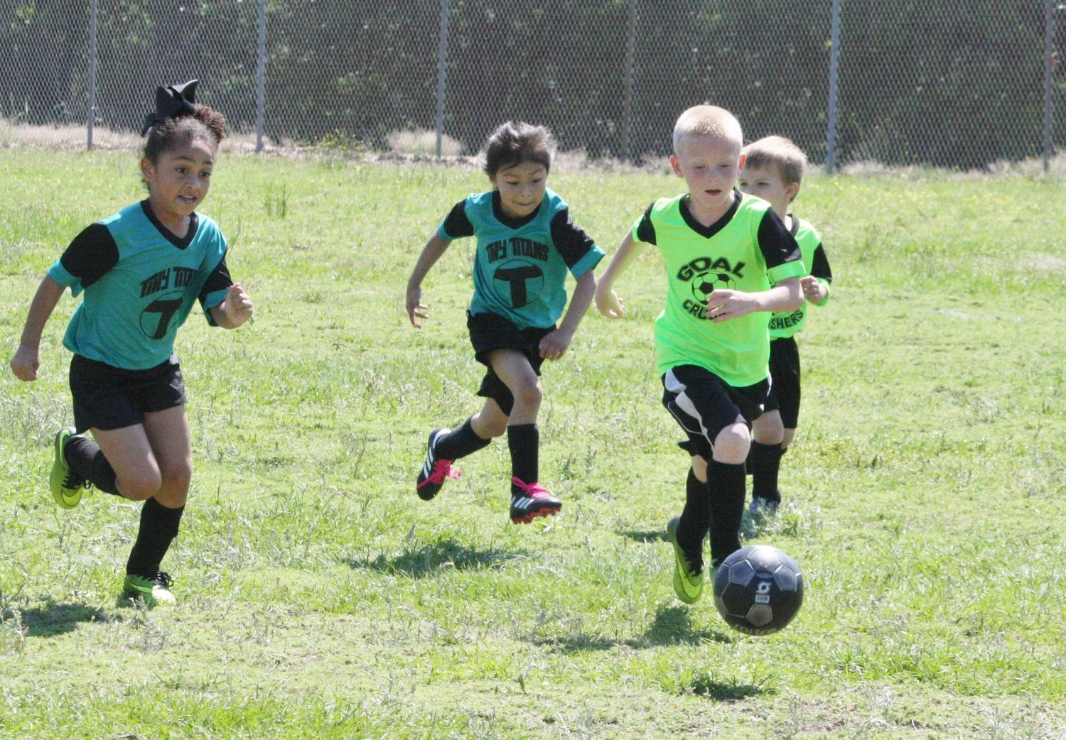 Local youths in hot pursuit of the soccer ball during a Saturday morning game of the Mineola Soccer Association.