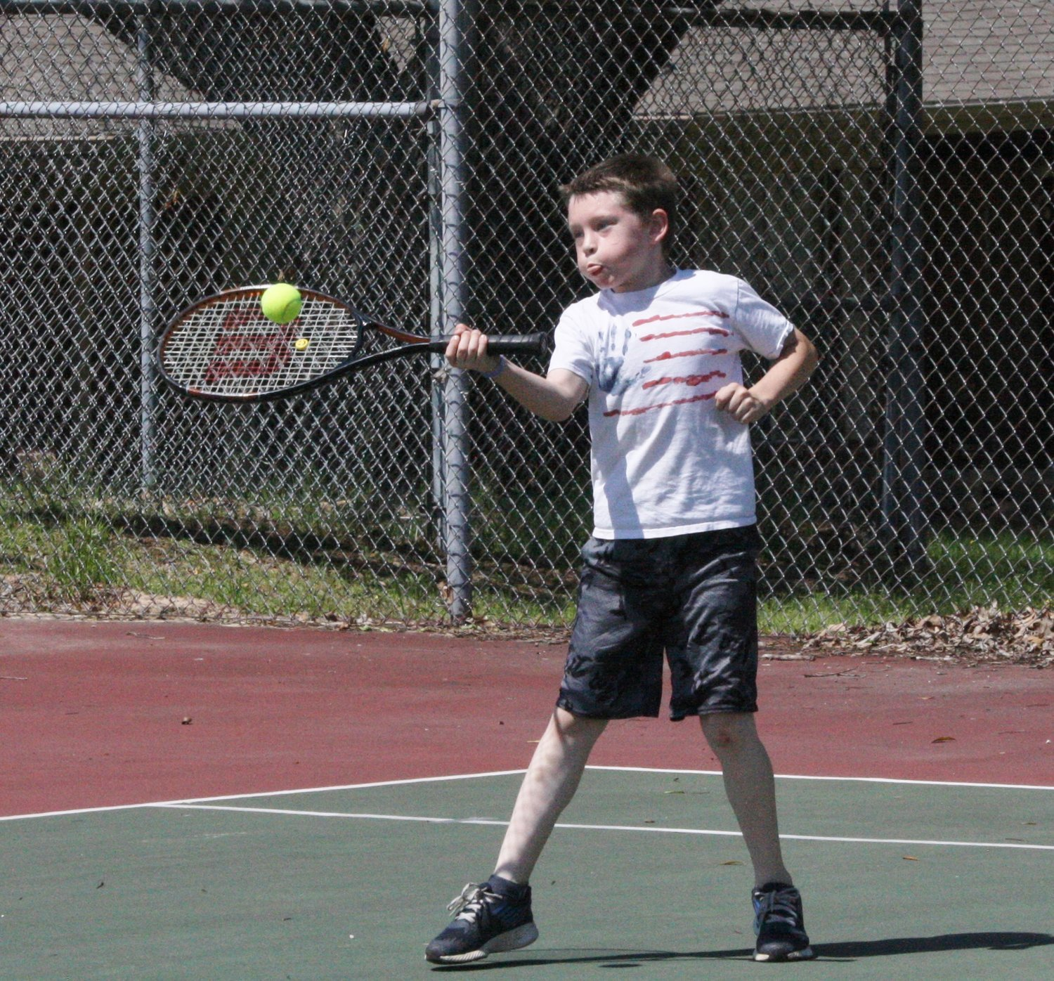 A youngster takes advantage of the great tennis courts available at the Mineola Civic Center grounds.
