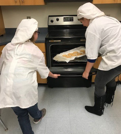 Quitman High School culinary arts students take one of their cooking projects out of the oven.