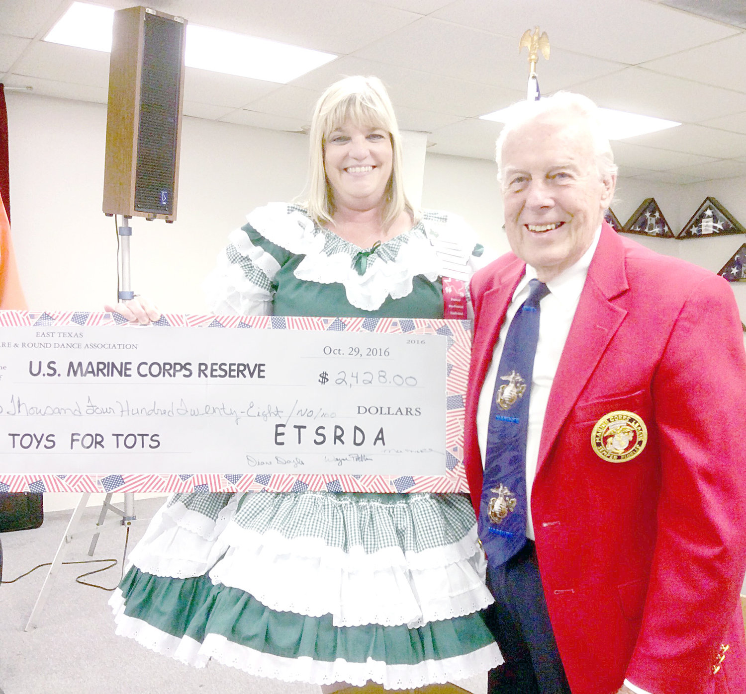 From left, Diane Doyle, president of East Texas Square & Round Dance Association, Inc. presents Larry Beason, chairman of the Marine Corp Reserve's Toys for Tots program, with a check for $2,428 along with four boxes of toys at the Square Dance Association's annual Toys for Tots Dance.  Beason said the donation would go towards making this a happy Christmas for a lot of East Texas children.