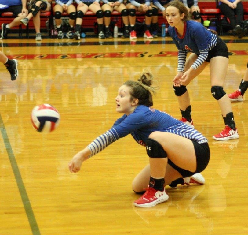 Lady Bulldog Lucy Brannon is focused like a laser on digging the ball in action against Van.
