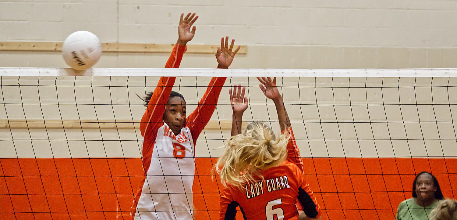 Mineola Lady Jacket Sabria Dean successfully blocks a shot at net under the watchful eye of Coach TaShara Everett.