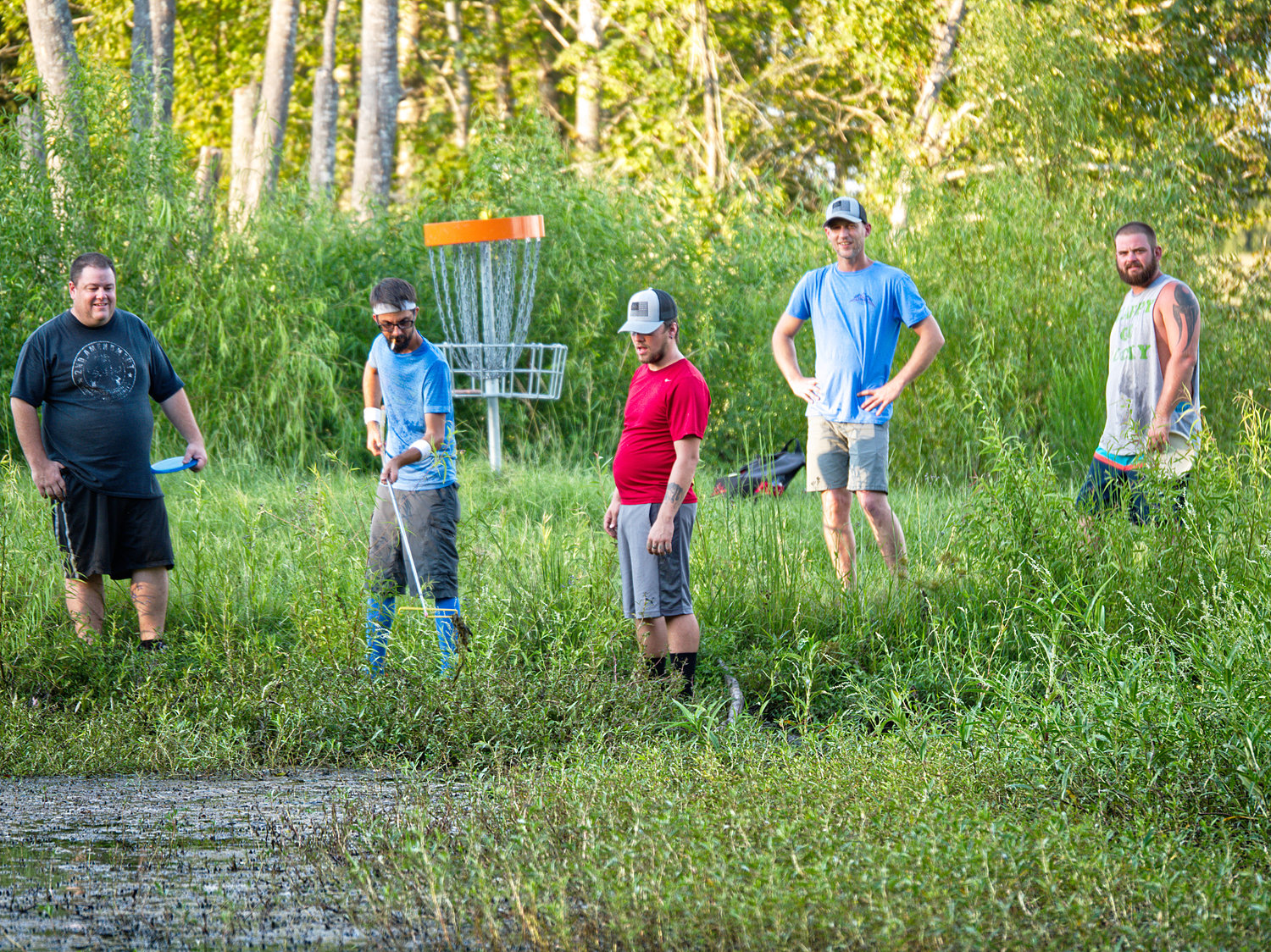 Hooked, Offline, SinkerDisc golfers try to rescue a putter from Grandpa's Pond next to a hole on The Preserve disc golf course Monday evening at the Mineola Nature Preserve.