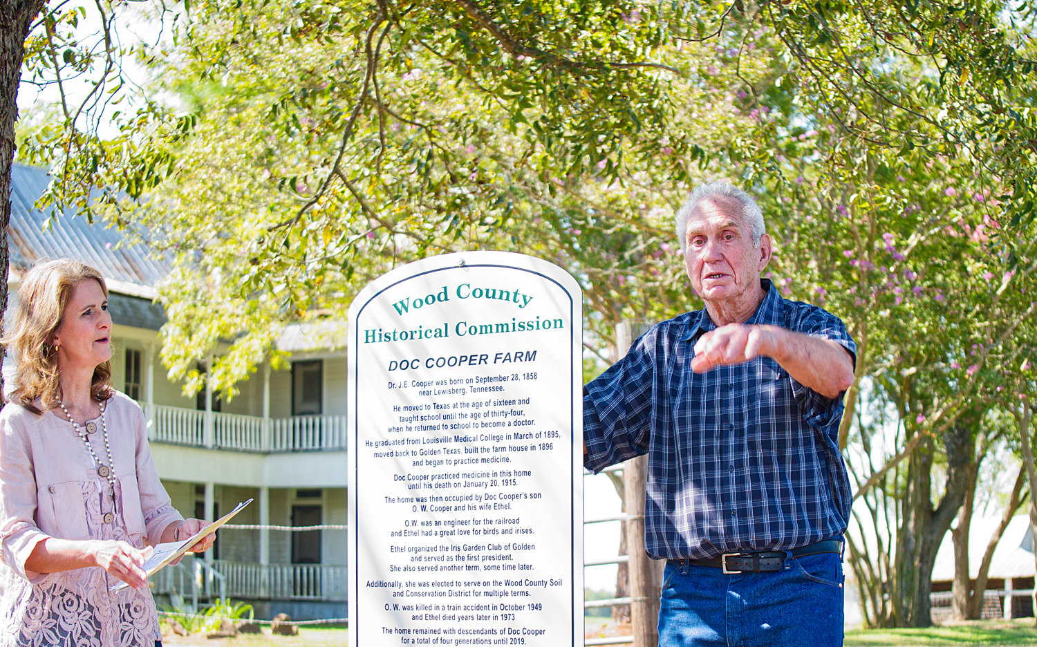 At last week's dedication of the Wood County historical marker at the Doc Cooper Farm, County Judge Lucy Hebron listens as Don Shamburger recalls stories of the old home.
