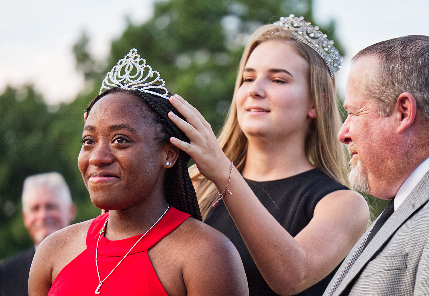 Lovely Wright is crowned Minoela 2019 homecoming queen by last year's queen, Lena Hughes, as Wright's escort, youth Pastor Kendall Banks looks on prior to Friday's football game with Farmersville (which the Yellowjackets won handily).