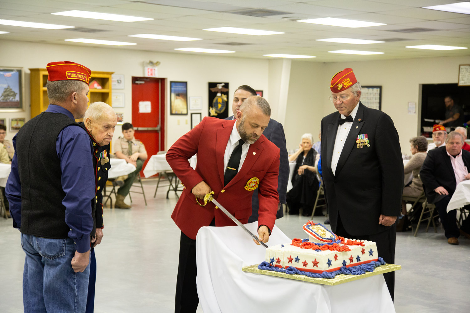 Marine Corps League Commandant Kelly Smith cuts the Marine Corps birth- day cake with the traditional Mameluke sword. The oldest Marine present, PFC James Krodel, and youngest Marine present, Lance Corporal Brandon Baade, watch with cake escorts James Biesheuvel and Mike Jernigan.
