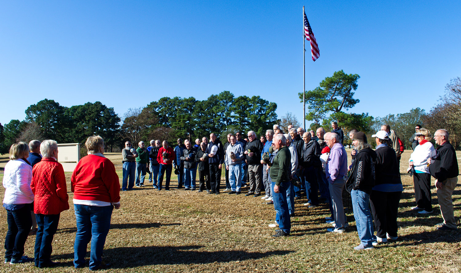 A group of military veterans gathers at the flag pole at the Mineola Country Club Friday morning for the singing of the National Anthem, along with a prayer and the Pledge of Allegiance, before teeing off in the club's annual veterans tournament (postponed from Monday, Nov. 11 due to inclement weather). Leading the singing were Shirley Frazier, Chris Black and Donna Kinstley.