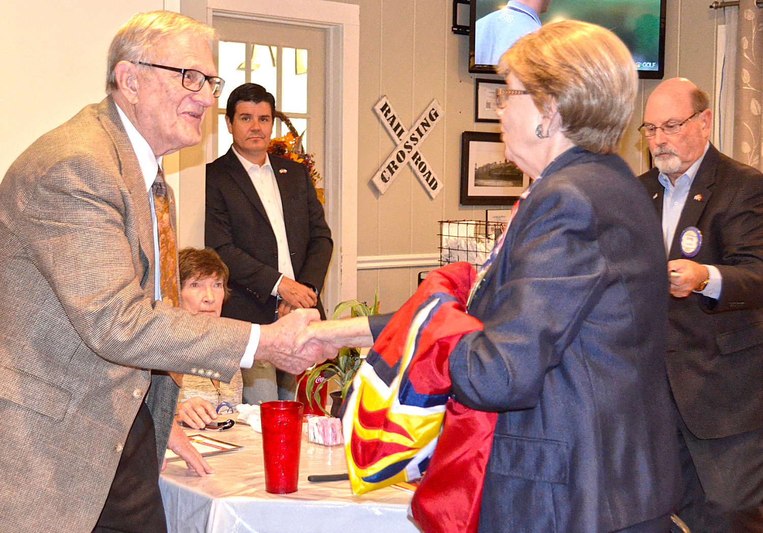 Bill Knight is congratulated by Mineola Rotary Club member Mary Lookadoo upon receiving the Honor and Remember Flags for his brothers who were killed in combat during Wolrd War Two and Vietnam.