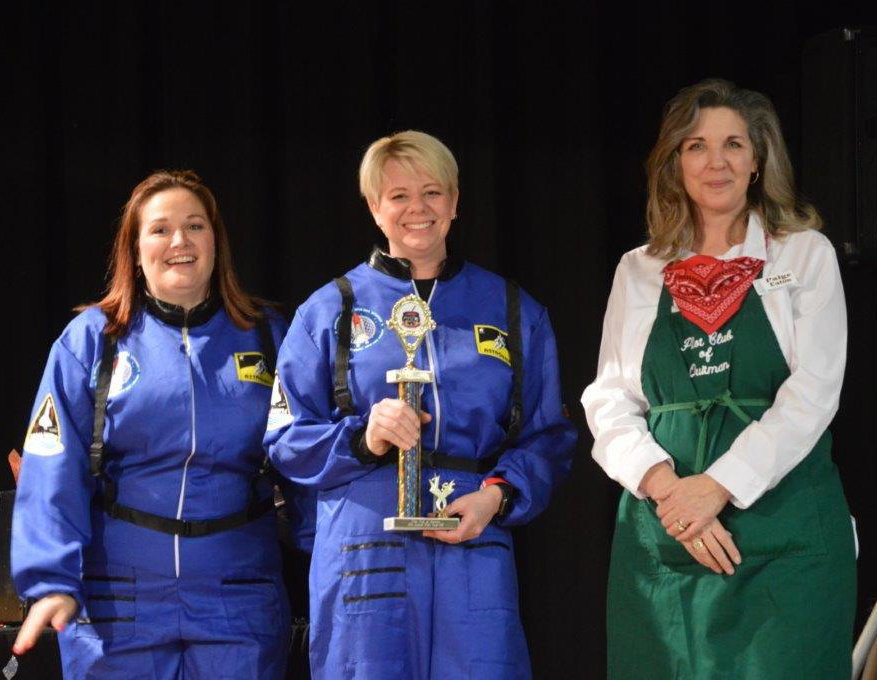 Speakeasy Coffee House representatives (left to right) Brandy Bradshaw and Kelly Keike accept the first place Showmanship Trophy from Paige Eaton at Friday's Quitman Pilot club Chili cook-Off.