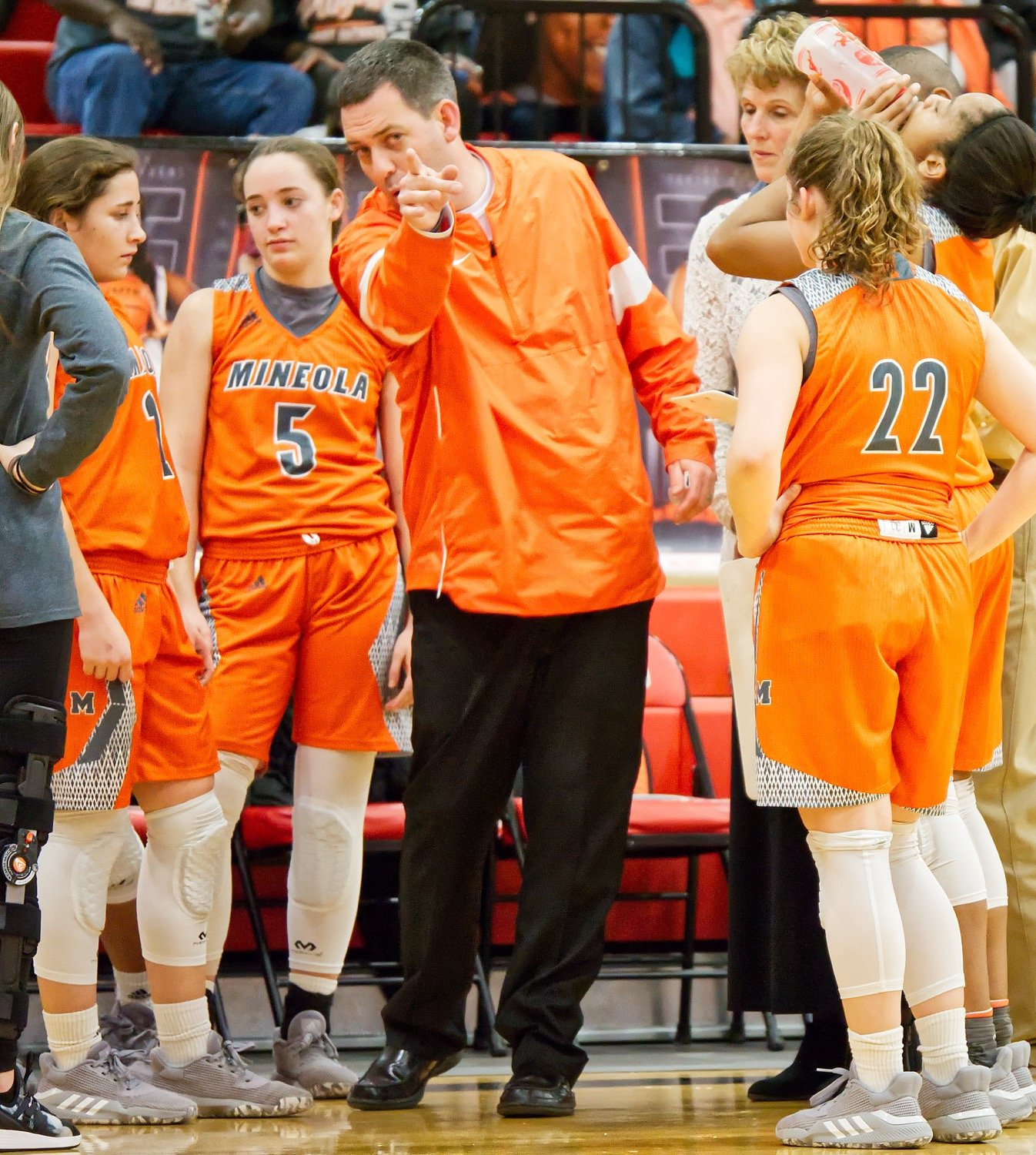Coach Brad Gibson makes a point to the huddled Ladyjackets during a timeout.