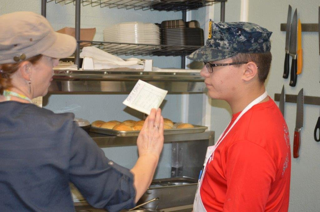 Your Appetites owner Ingrid Hightower works with one of the Naval Sea Cadets on an order during the group's training at the business.