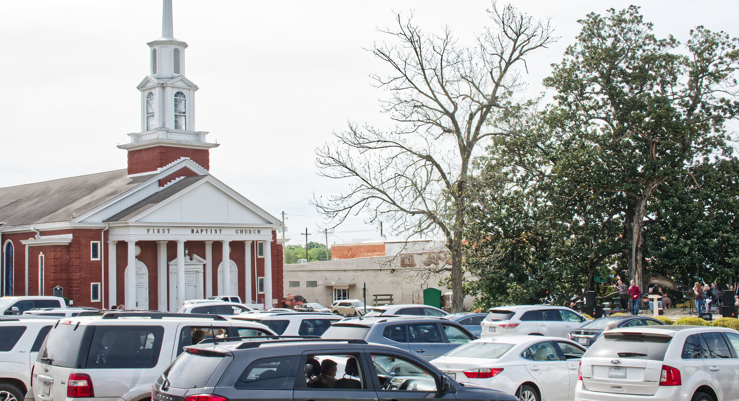 Dozens of churchgoers gathered in the parking lot across from their usual meeting place at the First Baptist Church in Mineola on Sunday, March 29, practicing social distancing while singing from their vehicles, led by an amplified praise team at Peterson Park.
