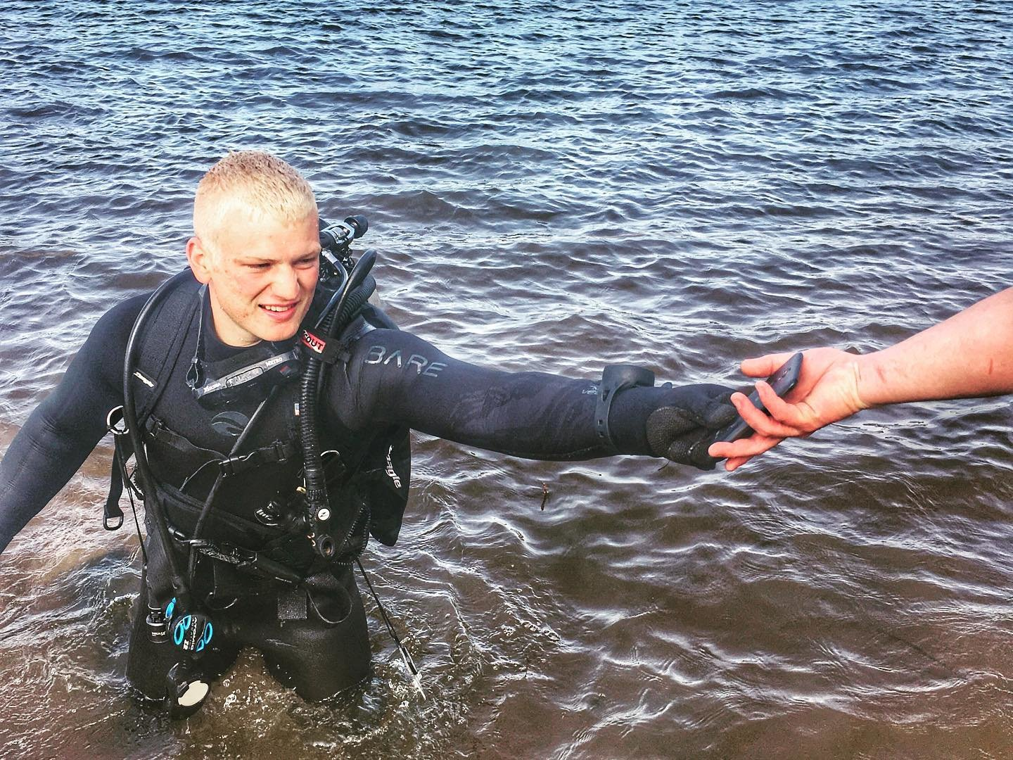 An International ALERT Academy dive team member retrieves a cell phone from Lake Quitman during the investigation of a drowning Monday.