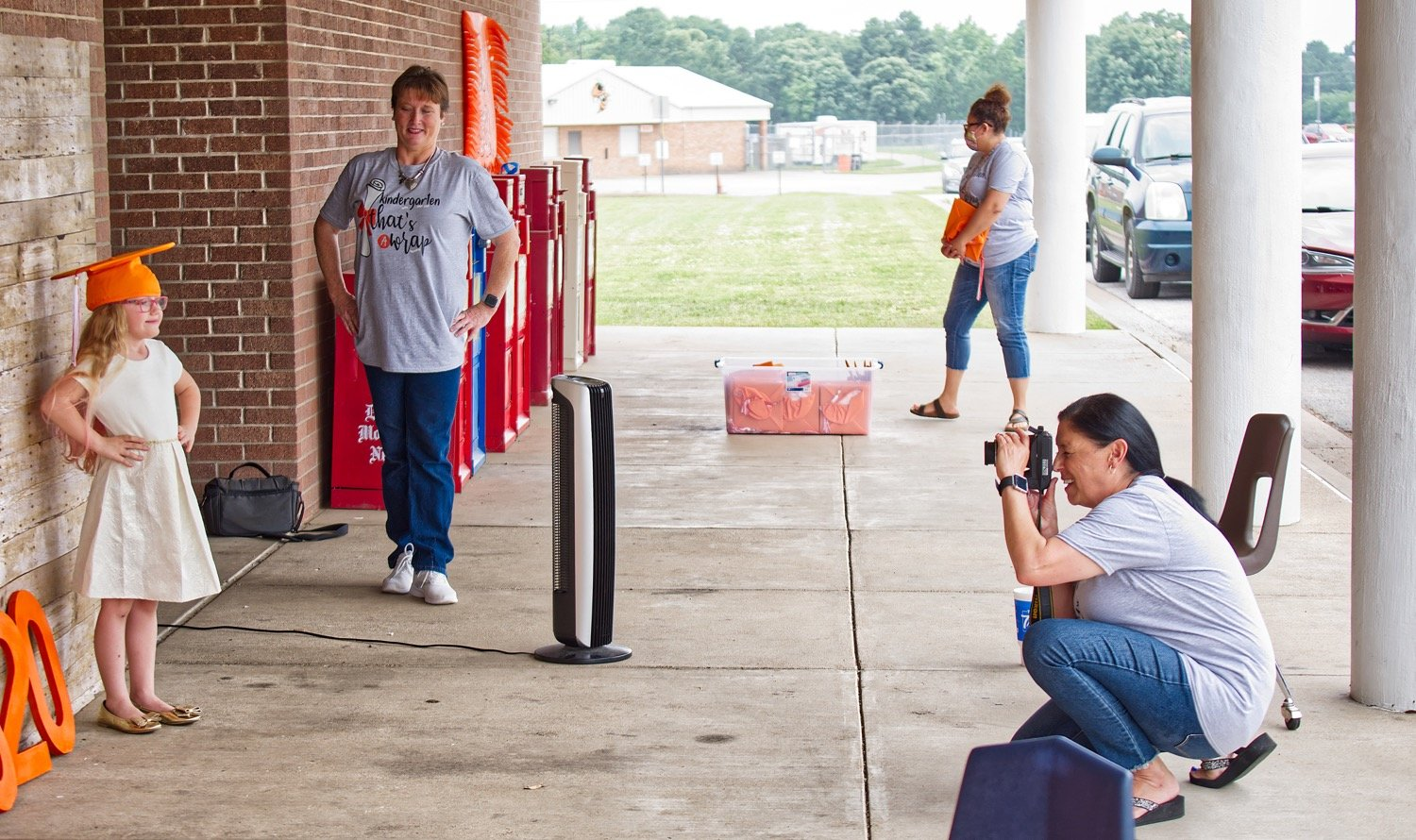 Mineola Primary School held a drive through graduation for kindergarten students last Thursday. Sylvia Harris takes a photo of Raelee Baber as kindergarten teachers Stacy Wedding and Raquel Palma assist.