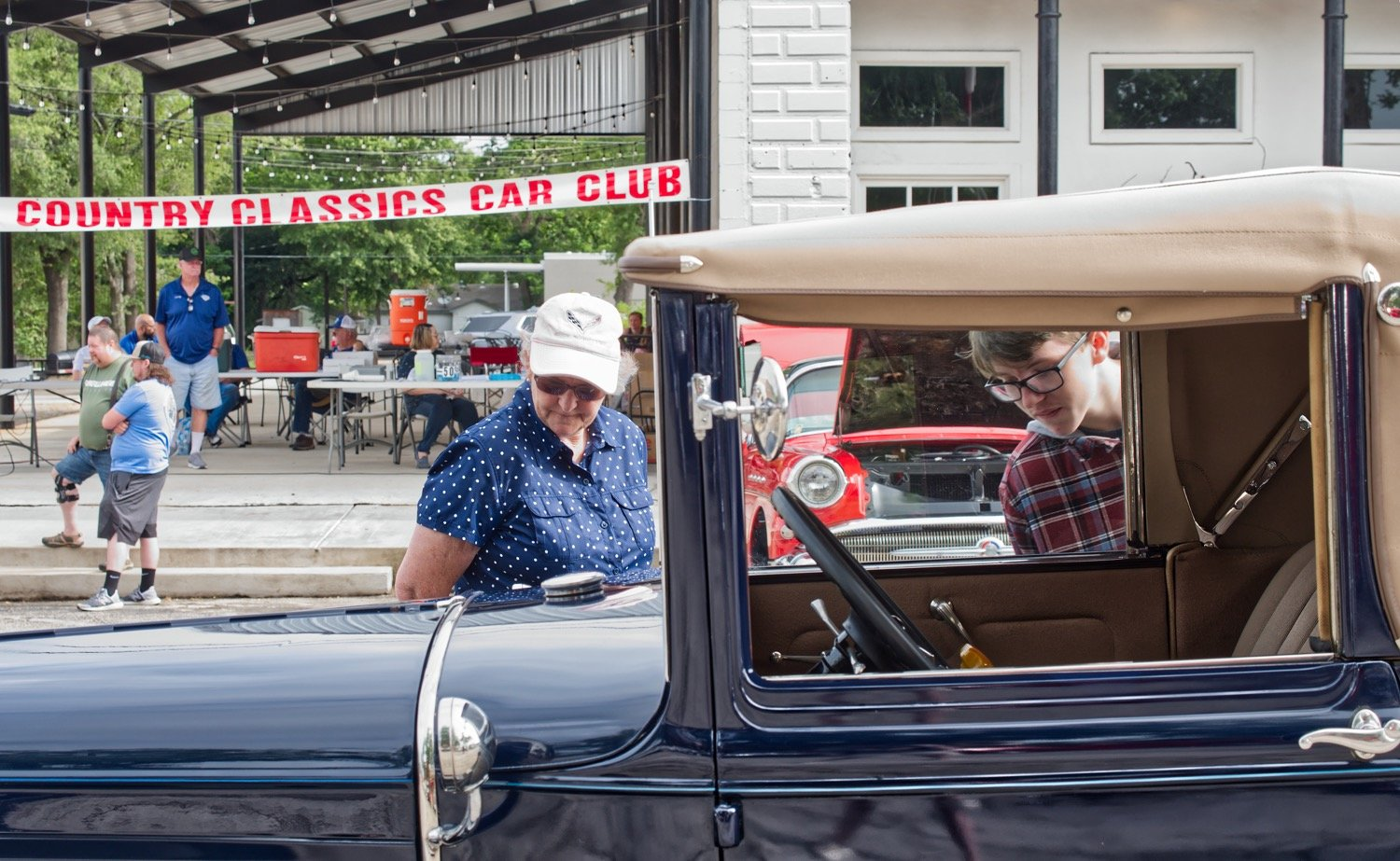 Janet Judkins and Jackson Friddle get a closeup look at an antique Ford Saturday morning at the courthouse square in Quitman. Lake Country Classic Cars put on the show which has been delayed by COVID-19 restrictions since March.