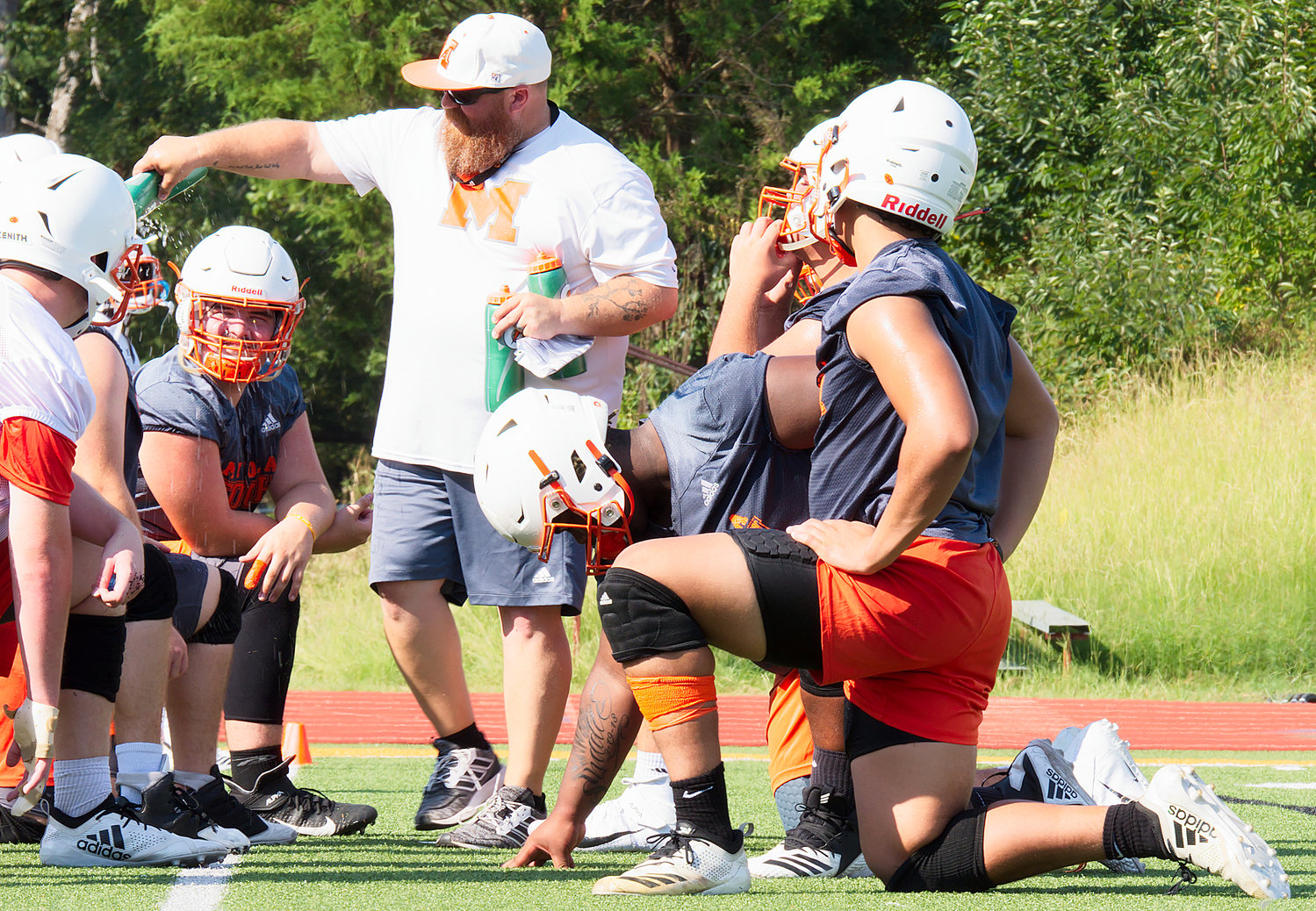 Mineola football players get a water break Monday morning.