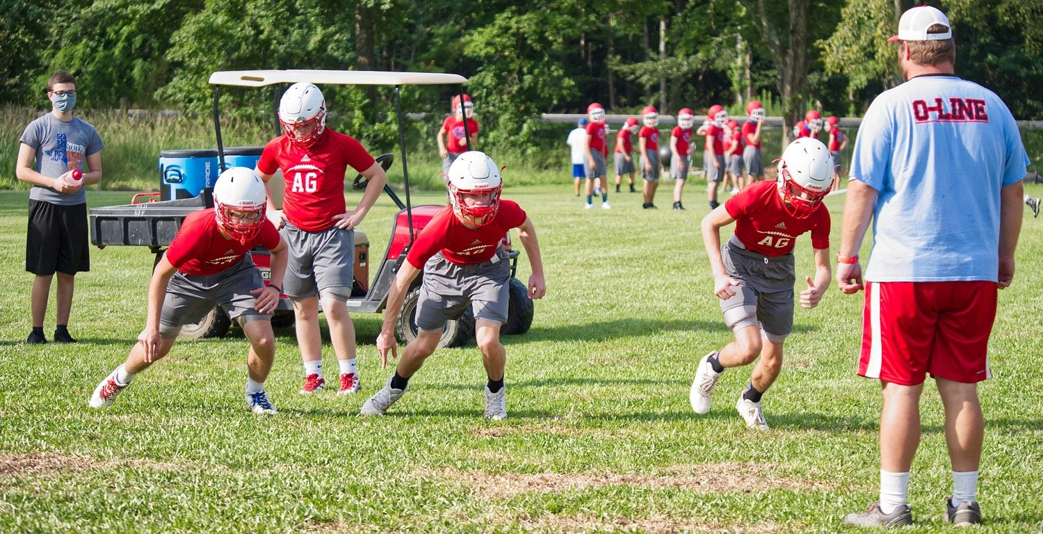 Alba-Golden linemen get in some drills during Tuesday morning practices under the eye of Coach Bobby Wells.