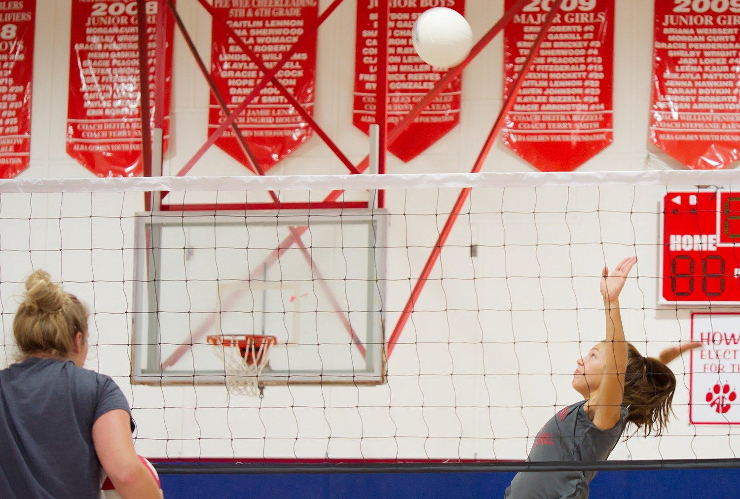 Alba-Golden volleyball Coach Jamie Webster observes as Hope Wiley takes part in spike drills Tuesday.