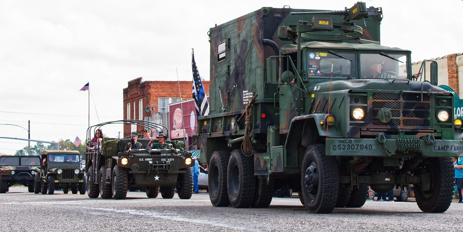 Jeeps, Hummers, and other military vehicles roll through downtown Mineola during the parade honoring veterans.