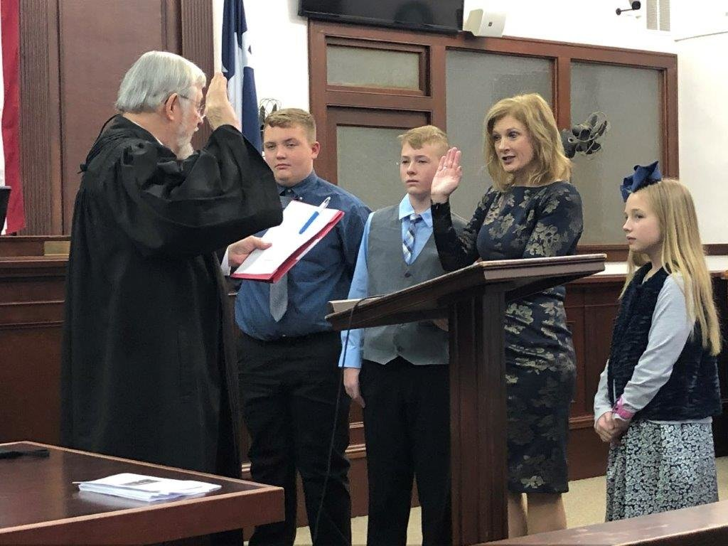 Former District Judge Timothy Boswell swears in Wood County District Attorney Angela Albers as her children (from left) Seth, Tate and Ella Catherine stand by her side.