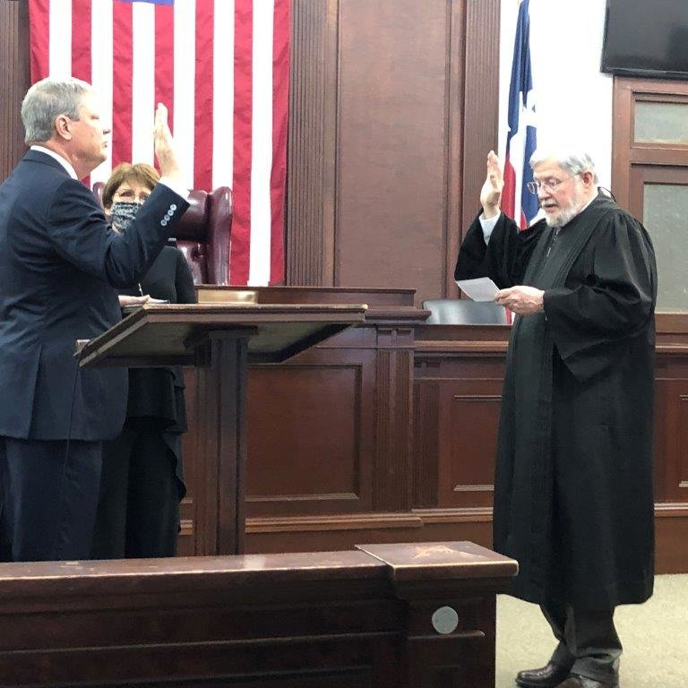 Brad McCampbell was sworn in as the new 402nd District Judge last Friday morning (Jan. 1) by the former judge Timothy Boswell as his wife Dawn McCampbell looks on.