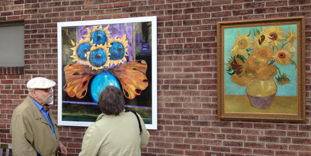 "Artists Peter Paone and Eileen Goodman look at Paone's piece of artwork ""Flowering Surprise"" outside of The Philadelphia Print Shop, 8441 Germantown Avenue. Next to Paone's artwork is Vincent van Gogh's ""Sunflowers,"" which inspired Paone at a young age to pursue a lifetime of painting. (Photo by Kevin Dicciani)"