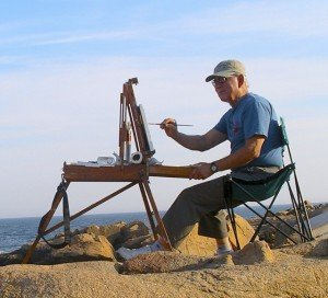 "Ed, 82, is seen painting on the orange rocks at Gloucester/Rockport, Massachusetts. He calls it ""the most beautiful rocky shore in New England except for Acadia."""
