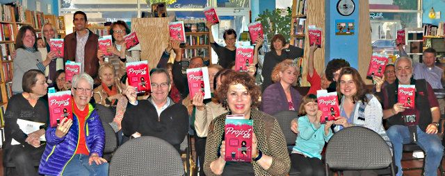 """Helen V. Reese (center) will be at Alma Mater Restaurant, 7165 Germantown Ave., on Wednesday, Feb. 10, 6 p.m., to read from her comic novel, """"Project Ex."""" Here she is seen with some of her fans at a book reading last November at Main Point Books in Bryn Mawr. (Photo by Steve Reese)"""