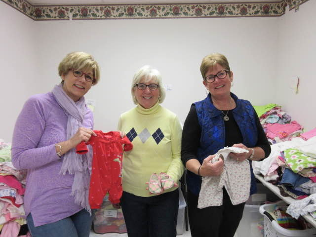 """Fran Wasserman, founder/director of The Baby Bureau (from left), along with volunteers Chris Reigel and Sharon Carney organize """"baby bundles"""" of clothing that they will send to impoverished families or who may have been victims of natural disasters."""