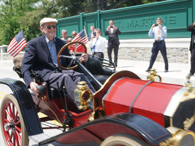 Joe Van Schrijver, drives a 1909 Hupmobile across the Willow Grove Avenue Bridge. The new bridge, which reopened to traffic earlier this year, was celebrated in an event last Wednesday, May 25. (Photo by Eric Dolente)