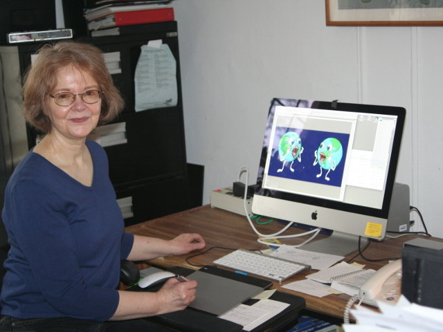 """Mt. Airy artist/author Kay Wood sketches by hand and adds color on the computer. Here she is adding color to sketches of planet Earth for """"The Big Belch."""" (Photo by Alicia M. Colombo)"""