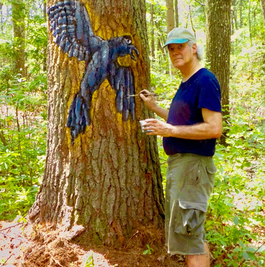Metz painting a raven on a tree. The painting will last for a few years and slowly disappear.