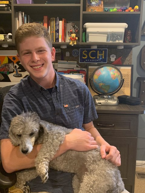 SCH junior Zach Schapiro with his dog in his home office.