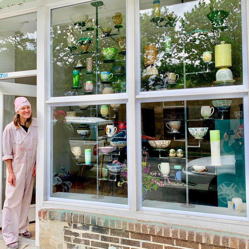 Liz Kinder admires her ceramic works in the window of her new studio at 7111 Emlen St. in West Mt. Airy.
